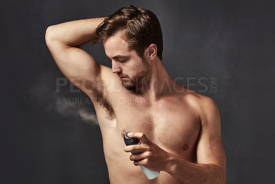 Buy stock photo Cropped shot of a handsome young man spraying deodorant on his armpit