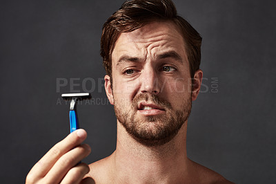 Buy stock photo Cropped shot of a handsome young man holding up a razor blade