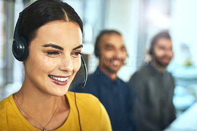 Buy stock photo Shot of a young call centre agent working in an office with her colleagues in the background