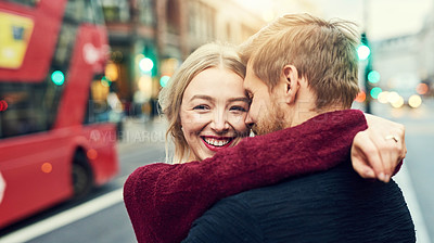Buy stock photo Shot of an affectionate young couple embracing in the city