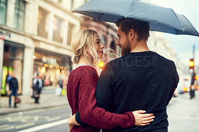 Buy stock photo Shot of a young couple standing under an umbrella in the city