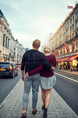 Buy stock photo Shot of a happy young couple going for a romantic walk in the city