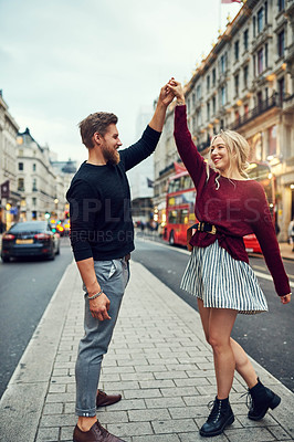 Buy stock photo Shot of a happy young couple dancing in the city