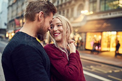 Buy stock photo Shot of an affectionate young couple sharing a romantic moment in the city