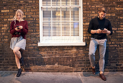 Buy stock photo Shot of a young man and woman standing opposite each other and using their smartphones