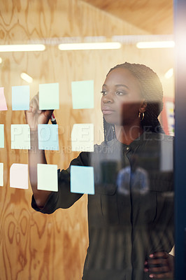 Buy stock photo Cropped shot of a young designer writing her ideas on adhesive notes