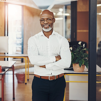 Buy stock photo Portrait of a mature businessman standing with his arms crossed in an office