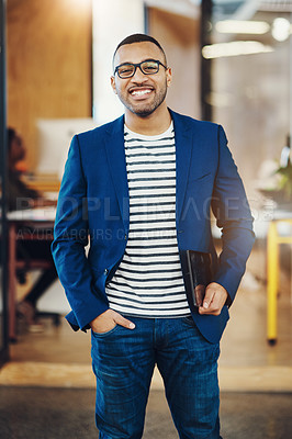 Buy stock photo Shot of a handsome young businessman standing in an office