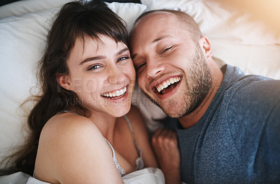 Buy stock photo Portrait of a happy young couple taking selfies together in bed
