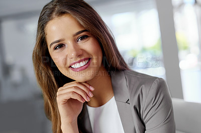 Buy stock photo Cropped portrait of a confident young businesswoman sitting with her hand on his chin in an office