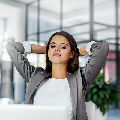 Buy stock photo Cropped shot of a young businesswoman sitting with her hands behind her head at her office desk