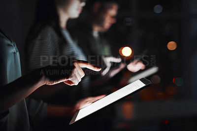 Buy stock photo Closeup shot of a group of businesspeople using digital devices in an office at night
