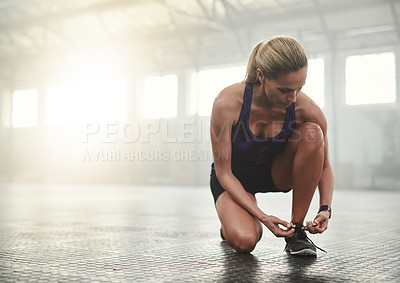 Buy stock photo Shot of an athletic young woman tying her shoelaces in the gym