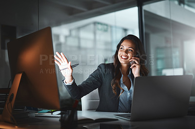 Buy stock photo Shot of a young businesswoman using a mobile phone and computer while working late in a modern office