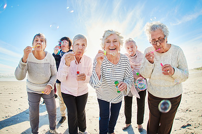 Buy stock photo Portrait of a group of happy senior women blowing bubbles at the beach