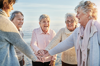 Buy stock photo Shot of a group of happy senior women joining their hands together at the beach