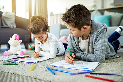 Buy stock photo Shot of two young kids lying on the floor with their coloring books