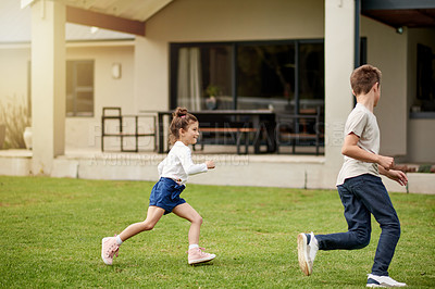 Buy stock photo Shot of a little girl chasing her older brother