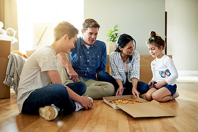 Buy stock photo Shot of a family taking a break from unpacking to have some pizza