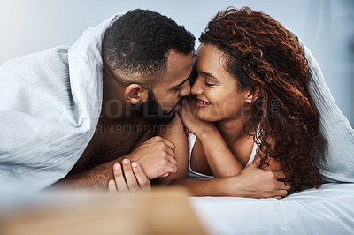 Buy stock photo Cropped shot of an affectionate young couple sharing an intimate moment while relaxing together in bed