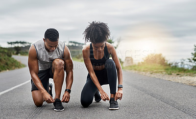 Buy stock photo Shot of a sporty young couple tying their shoelaces while exercising outdoors