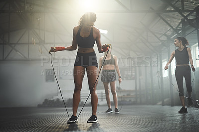 Buy stock photo Shot of women working out with skipping ropes at the gym