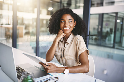 Buy stock photo Shot of a thoughtful  young businesswoman using a digital tablet at her desk in a modern office