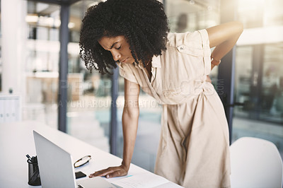 Buy stock photo Shot of a young businesswoman experiencing back pain while working in a modern office