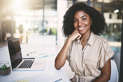 Buy stock photo Portrait of a confident young businesswoman working at her desk in a modern office