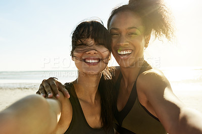 Buy stock photo Cropped portrait of two attractive and athletic young women taking selfies while out for a run on the beach
