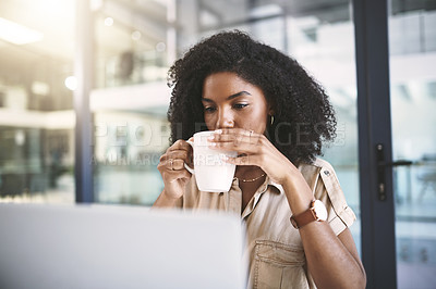 Buy stock photo Shot of a young businesswoman using a laptop and drinking coffee at her desk in a modern office