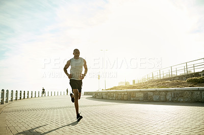 Buy stock photo Shot of a sporty young man out running on the promenade