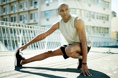 Buy stock photo Shot of a handsome young man doing his exercise routine outside