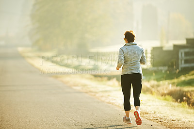 Buy stock photo Rearview shot of an unrecognizable mature sportswoman out for an early morning run in the park