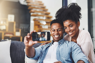 Buy stock photo Shot of a happy young couple taking selfies together on the sofa at home