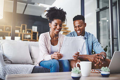 Buy stock photo Shot of a young couple going through their paperwork together at home