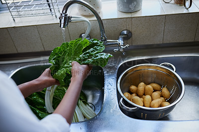 Buy stock photo Cropped shot of a woman rinsing spinach in a kitchen sink at home