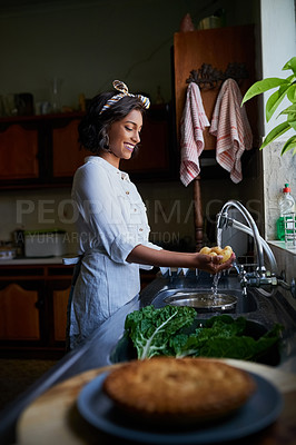 Buy stock photo Shot of a young woman rinsing potatoes in a kitchen sink at home
