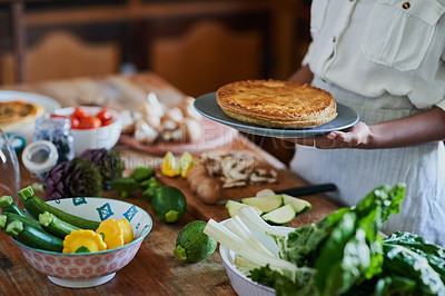 Buy stock photo Cropped shot of a woman serving a freshly baked pie at home