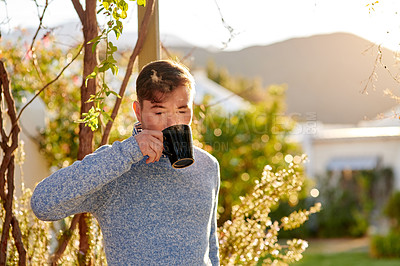 Buy stock photo Shot of a young man having a cup of coffee outside in a garden