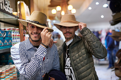 Buy stock photo Portrait of two young men trying on hats in a store