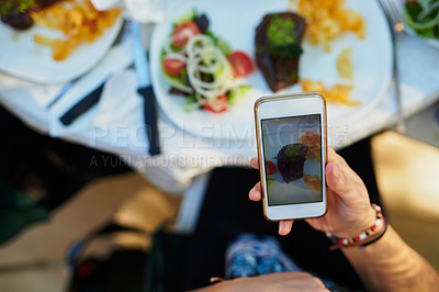 Buy stock photo Cropped shot of a man taking a picture of his meal on a smartphone