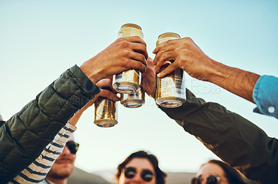 Buy stock photo Low angle shot of a group of young friends cheersing with beers while enjoying their day out on the beach