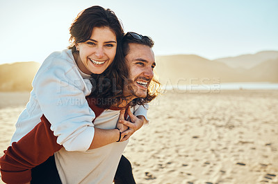 Buy stock photo Cropped shot of a handsome young man piggybacking his girlfriend while enjoying their day at the beach