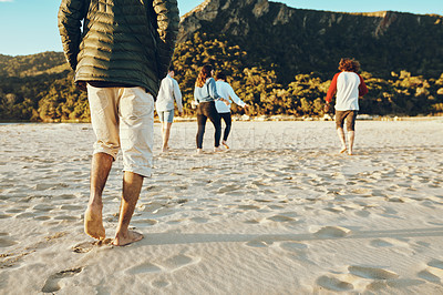 Buy stock photo Rearview shot of a group of unrecognizable young friends enjoying their day on the beach