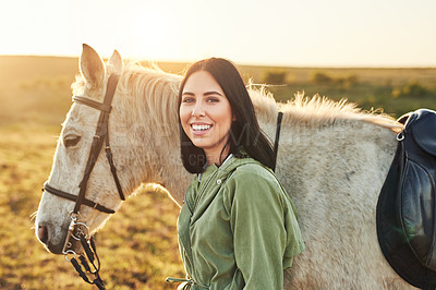 Buy stock photo Shot of a young woman spending time with her horse on a farm