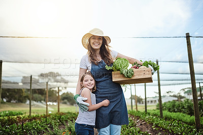 Buy stock photo Cropped shot of a young mother and her little daughter working on the family farm