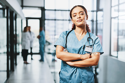 Buy stock photo Portrait of a young nurse standing with her arms crossed in a hospital
