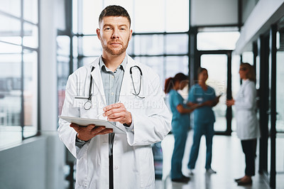 Buy stock photo Portrait of a mature doctor using a digital tablet in a hospital