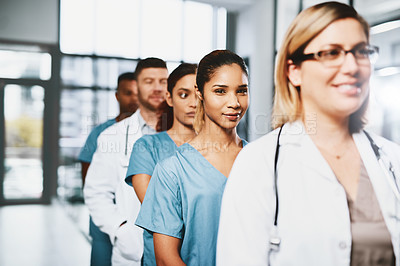 Buy stock photo Portrait of a young nurse standing in a line amongst her colleagues in a hospital